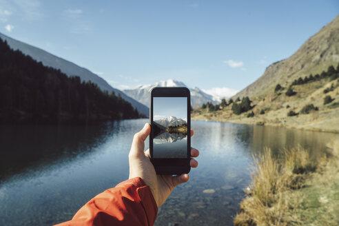France, Pyrenees, Pic Carlit, man taking a picture at mountain lake - KKAF00159