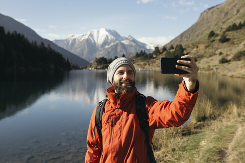 France, Pyrenees, Pic Carlit, hiker taking a selfie at mountain lake - KKAF00162