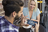 Young man with girlfriend taking cell phone picture at outdoor cafe - WEST22140