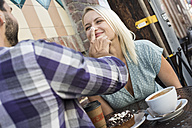Playful young man with girlfriend at outdoor cafe - WEST22143
