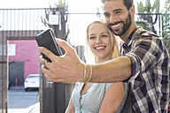 Happy young man with girlfriend taking a selfie - WEST22146