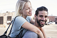 Happy young man carrying girlfriend piggyback - WEST22161