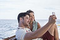 Happy couple on a boat trip taking a selfie - WESTF22221