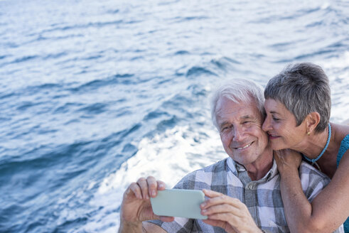 Happy couple on a boat trip taking a selfie - WESTF22239