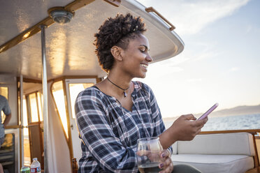 Smiling young woman on a boat checking cell phone - WESTF22278