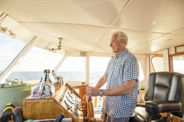 Confident senior man steering a boat - WESTF22290