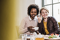 Two young women using cell phone in a cafe - UUF09463