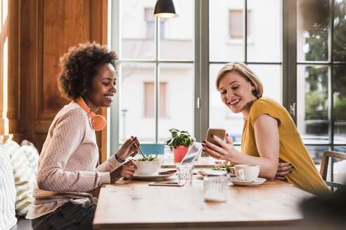 Two young women with cell phone meeting in a cafe - UUF09472