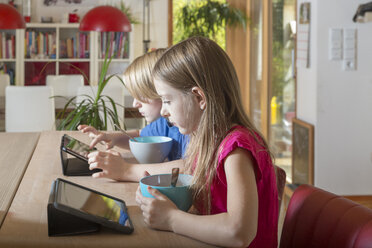 Boy and girl using tablets at breakfast table - SARF03086