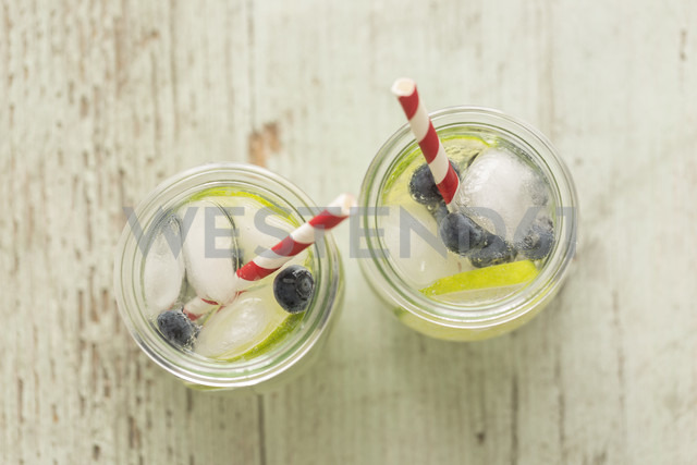Glasses of infused water with lime, blueberries and ice cubes - JUNF00708