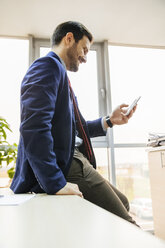 Smiling young businessman in office looking on cell phone - ZEDF00460