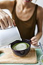 Woman preparing matcha latte at home - VABF00879