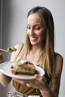 Woman eating vegan matcha cake - VABF00894