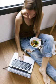 Woman at home eating vegetables with chopsticks and using laptop - VABF00897