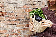 Smiling woman holding basket with fresh vegetables - VABF00903