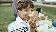 Portrait of smiling boy holding sandwich with his family in background - DAPF00524