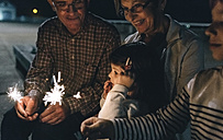Grandparents with grandchildren holding sparklers at night - DAPF00527