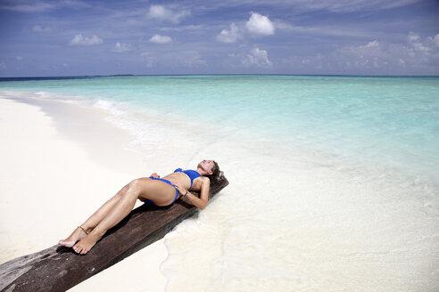 Maldives, woman sunbathing on a log on a beach - DSGF01245