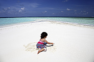 Maldives, girl on beach at shallow water - DSGF01269