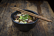 Bowl of miso soup with organic tofu, shitake mushrooms, leek and parsley on dark wood - LVF05699
