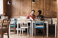 Young man and woman having a meeting in a cafe - UUF09501