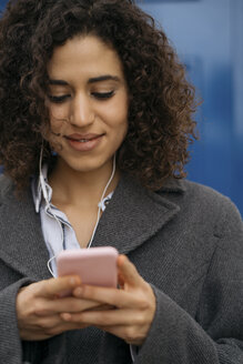 Smiling young woman with earphones looking at mobile phone - KKAF00171