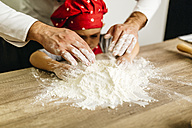 Father and son kneading dough together - JRFF01098