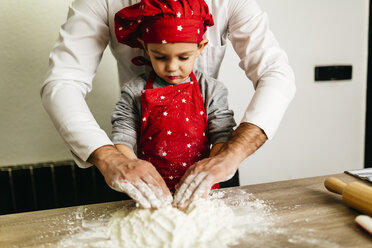 Father and son kneading dough together - JRFF01101