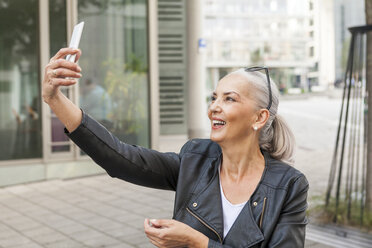 Smiling mature woman taking selfie with smartphone - JUNF00724