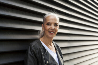 Portrait of smiling mature woman in front of black wall - JUNF00727