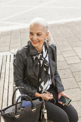 Fashionable mature woman sitting on bench watching something - JUNF00736