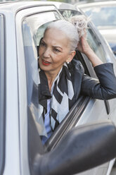 Portrait of businesswoman leaning out of car window - JUNF00739