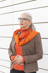 Portrait of fashionable mature woman standing in front of white wall - JUNF00748