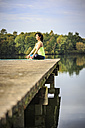 Woman practicing yoga on jetty at a lake - VTF00570