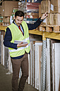 Man in warehouse supervising stock - ZEDF00464