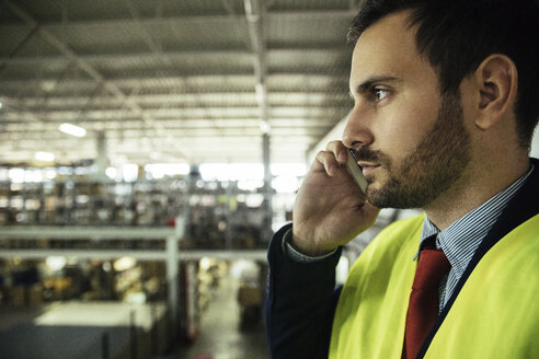 Man on cell phone in factory - ZEDF00467