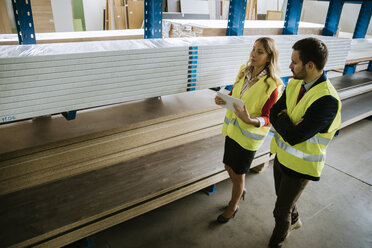 Man and woman in warehouse supervising stock - ZEDF00470