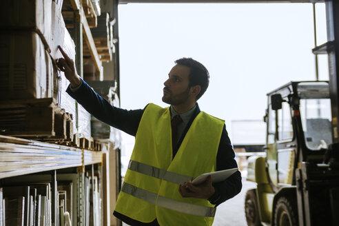 Man in warehouse supervising stock - ZEDF00473