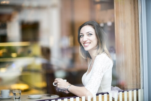 Young woman sitting in coffee shop, drinking coffee - TAMF00890