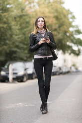 Young woman in the street using smart phone - TAMF00896