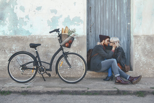 Young couple in love kissing on door step next to a bike - RTBF00559