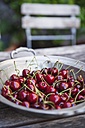 Zinc bowl of sweet cherries on garden table - GWF04919