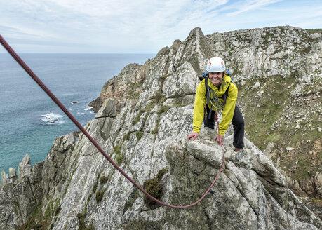 UK, Cornwall, smiling woman climbing on Commando Ridge - ALRF00746