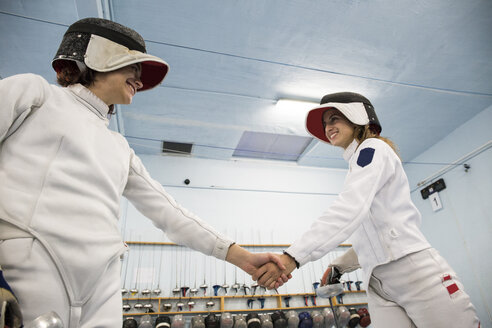 Female fencers shaking hands after a fencing match - ABZF01623
