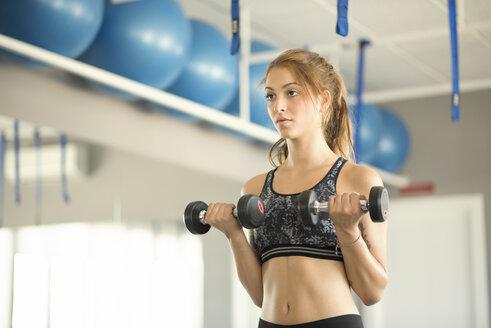 Woman training biceps in gym - JASF01385