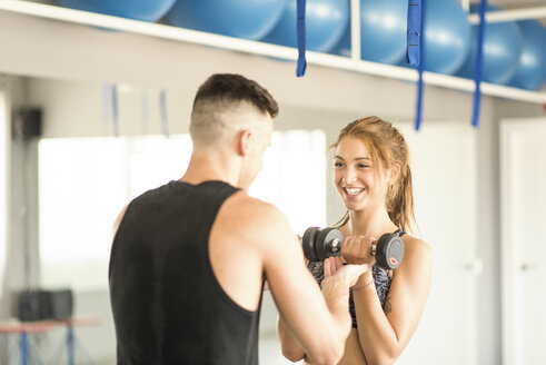 Personal trainer helping woman lifting weights - JASF01388