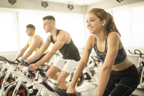 People exercising on spinning bikes in gym - JASF01397