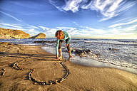 Spain, Almeria, woman scratching heart in the sand of beach at Cabo de Gata Natural Park - DSGF01350