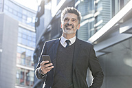 Smiling businessman outdoors with cell phone - TCF05214