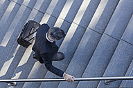 Businessman walking with suitcase on stairs - TCF05226